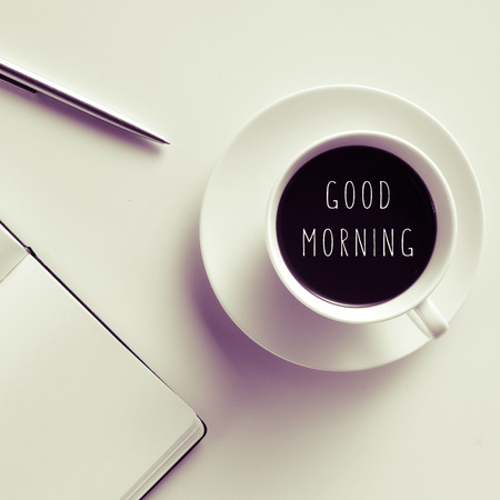 politeness: high-angle shot of a white table with a pen, a notebook, and a cup of coffee with the text good morning written in it