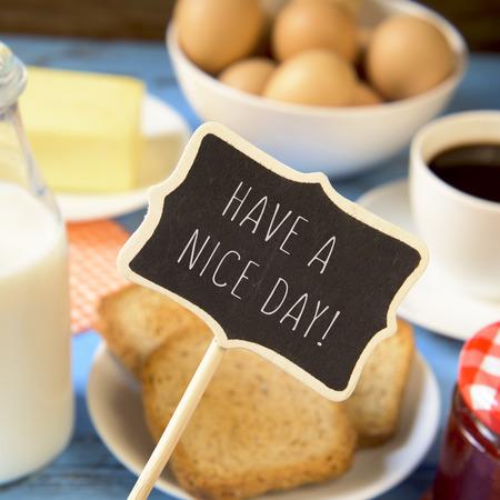 comida rica: una pizarra con el texto tenga un buen día y una mesa de madera de color azul con una botella de leche, una taza de café, algunas tostadas en un plato, un tarro de mermelada y una barra de mantequilla Foto de archivo