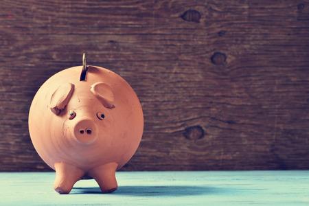 dinero: un banco de barro alcancía con una moneda en su agujero, en una superficie rústica azul