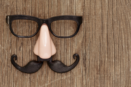a fake mustache, nose and eyeglasses on a rustic wooden surface
