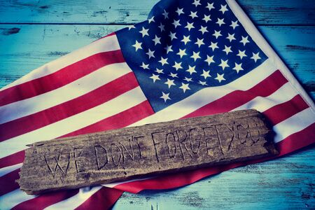 not forget: the text we do not forget you carved in a piece of old wood and a flag of the United States, on a rustic blue wooden background Stock Photo
