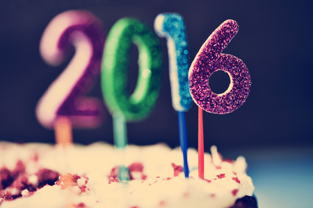 message: closeup of four glittering numbers of different colors forming the number 2016, as the new year, topping a cake
