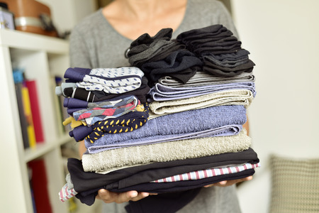 closeup of a young man carrying a pile of different folded clothes
