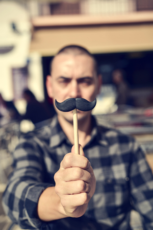 manly man: a young caucasian man holding a fake moustache in a stick in front of his face