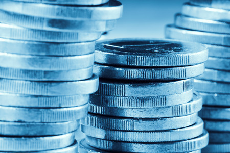 monetary devaluation: closeup of some piles of coins of one euro, blue toned Stock Photo