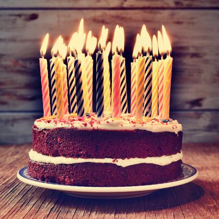 pastel cumpleaños: un pastel cubierto con algunas velas encendidas antes de soplar la tarta, sobre una mesa de madera rústica, con un efecto filtrada
