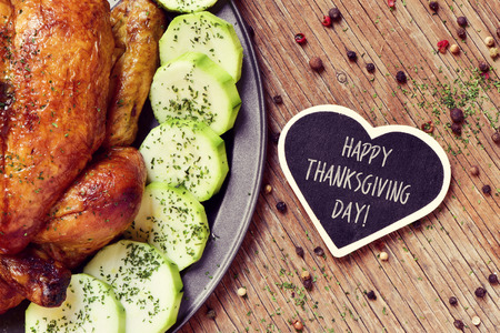 thanksgiving: closeup of an appetizing roast turkey in a tray with vegetables and a heart-shaped chalkboard with the text happy thanksgiving day on a wooden rustic table Stock Photo
