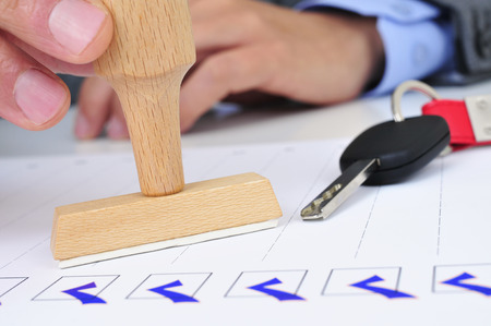 car retailer: closeup of a young caucasian man in his office with a rubber stamp and a car key on his desk Stock Photo