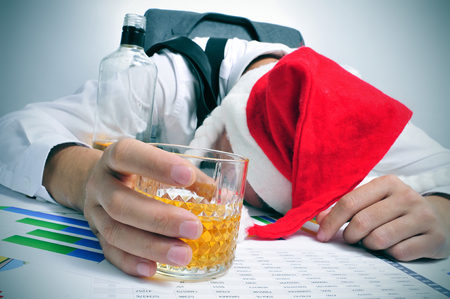 christmas concept: a man with a santa hat sleeping in his desk after an office christmas party