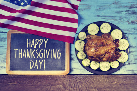 american cuisine: a flag of the United States, a chalkboard with the text happy thanksgiving day and a roast turkey in a tray with vegetables on a blue wooden rustic surface Stock Photo