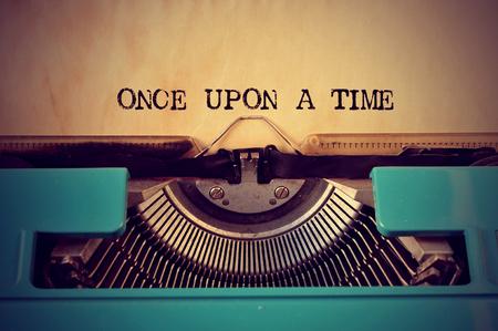 literatura: primer plano de una m�quina de escribir retro azul y el texto �rase una vez escrita con �l en un papel de color amarillento