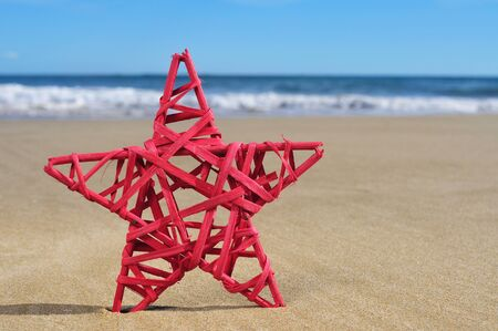 christmas star: closeup of a rustic red christmas star on the sand of a beach Stock Photo