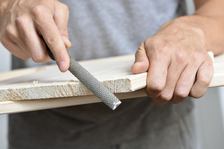 rasp: closeup of a young caucasian man filing a wooden board with a rasp