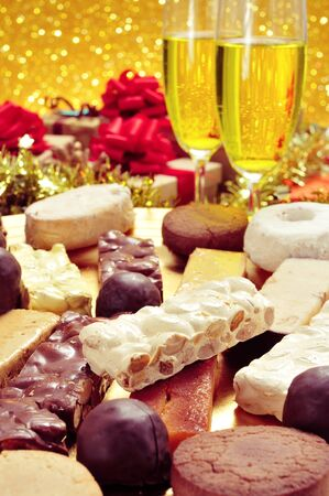 spain: a tray with different turron, mantecados and polvorones, typical christmas sweets in Spain, on a set table with some glasses with champagne and some gifts