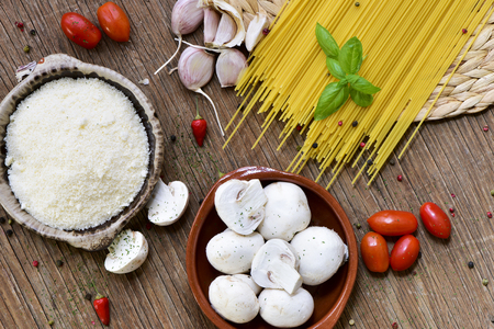 queso rayado: high-angle shot of a rustic wooden table with the ingredients to prepare a recipe of pasta, such as grated cheese, garlics, mushrooms, cherry tomatoes and spaghetti