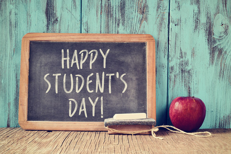 literacy instruction: the text happy students day written in a chalkboard, placed on a rustic wooden school desk next to an eraser and a red apple