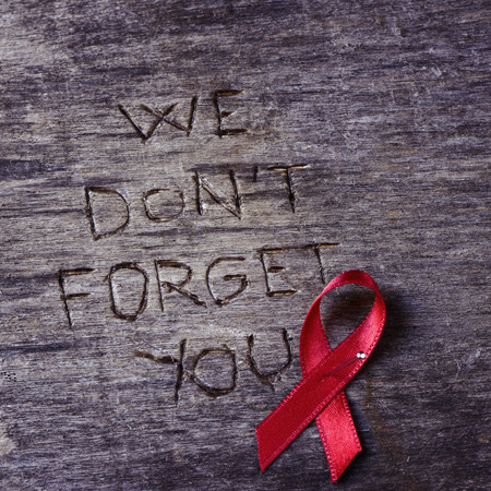 hiv ribbon: the text we do not forget you carved on a rustic wooden surface and a red ribbon for the fight against AIDS