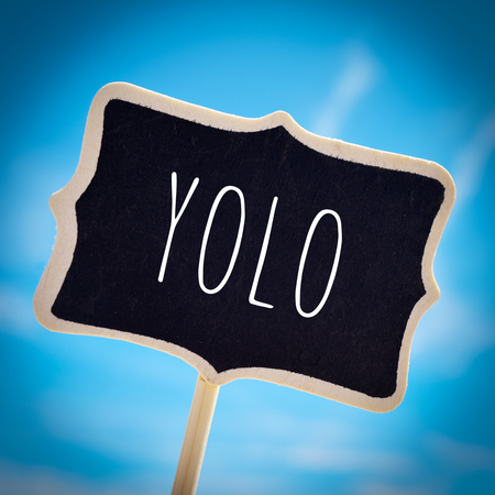 generation y: closeup of a signboard with the word yolo, for you only live once, over the blue sky, with a slight vignette added