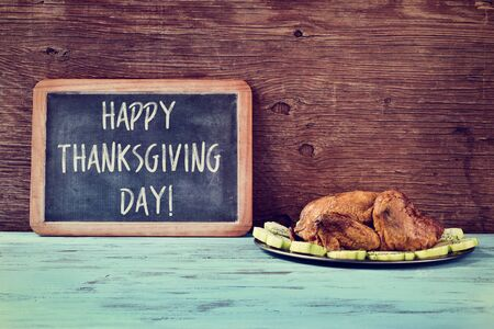 roast turkey: a roast turkey in a tray with vegetables and a chalkboard with the text happy thanksgiving day written in it on a blue wooden rustic table Stock Photo