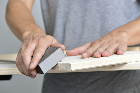 sanding block: closeup of a young caucasian man sanding a wooden board with a sanding block Stock Photo