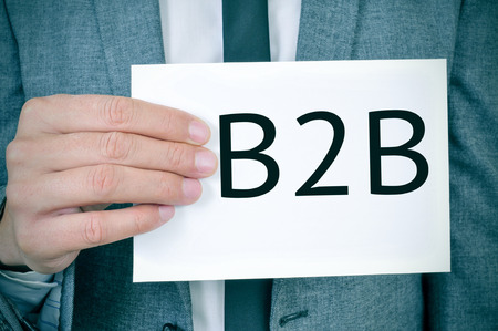 headman: closeup of a young caucasian man in a grey suit showing a signboard with the word B2B written in it