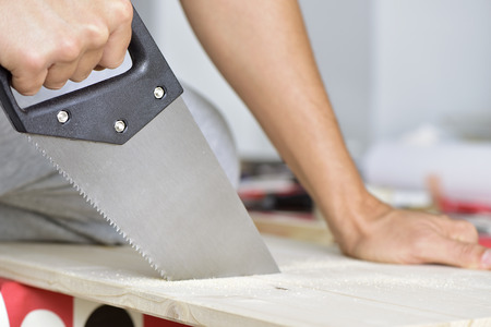 handsaw: closeup of a young caucasian man sawing a wooden board with a handsaw