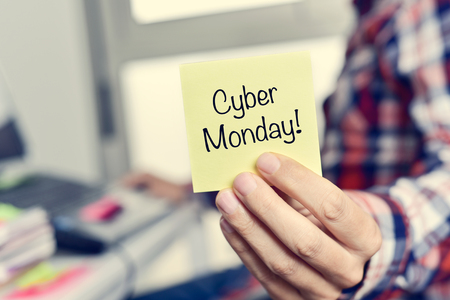 online shoppping: closeup of a young caucasian man wearing a plaid shirt sitting at his desk showing a yellow sticky note with the text cyber monday written in it Stock Photo