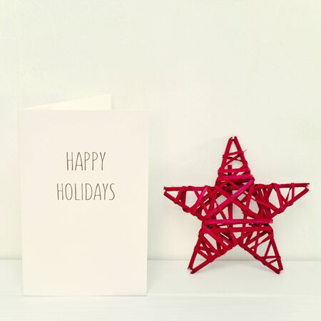 minimal: a rustic red Christmas star and a white greeting card with the text happy holidays in a white scene Stock Photo