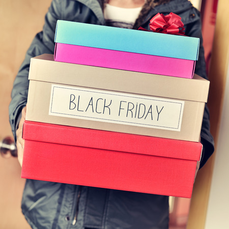 consumerism: closeup of a young caucasian man holding a pile of boxes, one of them with the text black friday written in it Stock Photo