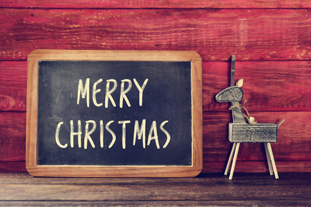 wooden reindeer: a chalkboard with the text merry christmas written in it and a rustic wooden reindeer placed on a wooden surface