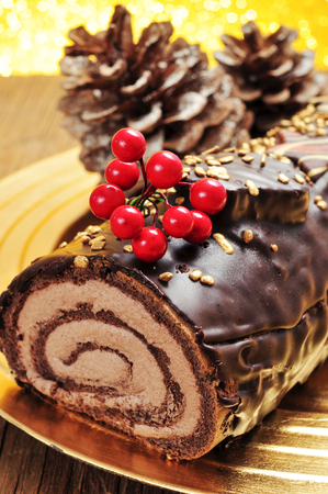 logs: a yule log cake, traditional of christmas time, in a golden tray with some natural ornaments, such as pinecones
