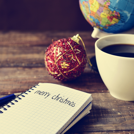 migrated: closeup of a notebook with the text merry christmas written in it on a rustic wooden table with a red and golden christmas bauble, a cup of coffee and a globe