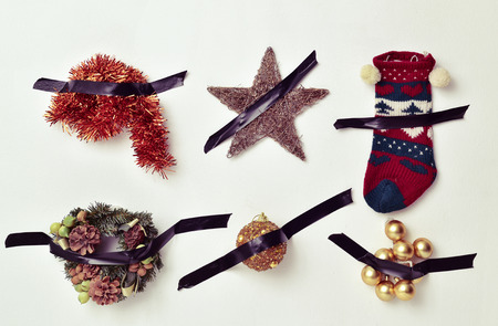 singular: some different christmas ornaments, such as tinsel, a star, a stocking or baubles, attached to a white wall with black tape