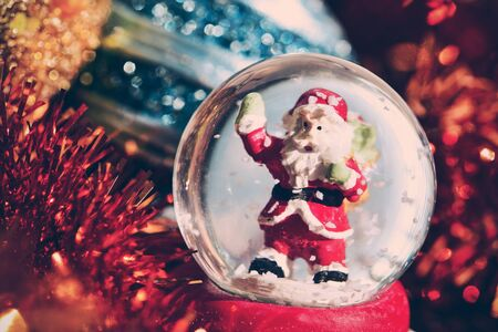 snowdome: closeup of a christmas snow globe with a santa claus in it and some other ornaments, such as baubles and tinsel Stock Photo