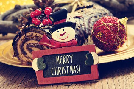 yule log: a yule log cake, traditional of christmas time, and a snowman-shaped chalkboard with text merry christmas written in it