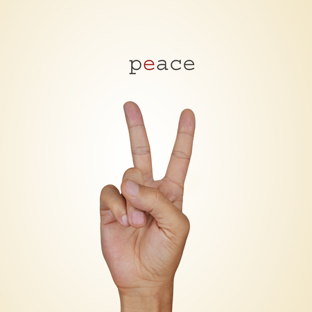 v shape: closeup of the hand of a young man giving the V sign and the word peace on a beige background