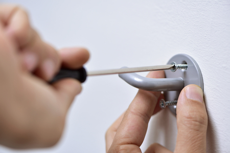 screwing: closeup of a young caucasian man screwing a hook in the wall with a screwdriver