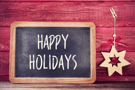 feriado: una pizarra con las buenas fiestas de texto escritos en ella y una estrella de navidad de madera sobre una superficie de madera rústica roja