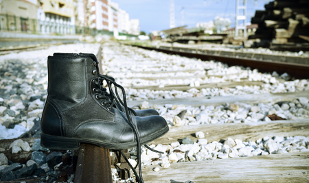 railroad tracks: closeup of a pair of mens boots abandoned on the railroad tracks Stock Photo