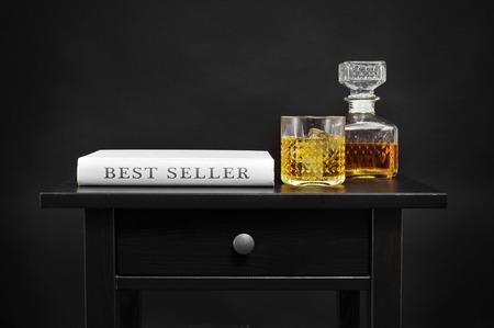 libros antiguos: un libro con el vendedor mejor texto escrito en su columna vertebral, y una botella y un vaso lowball con el licor en una mesa de negro, sobre un fondo negro