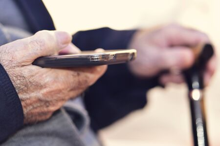 societies: closeup of an old caucasian man with a walking stick in his hand using a smartphone