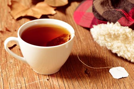 taza de té: cerca de una taza de cerámica blanca con una bolsa de té o té de hierbas que se remoja en agua caliente, sobre una mesa de madera rústica Foto de archivo