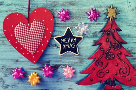 wooden surface: a star-shaped chalkboard with the text merry xmas written in it on a blue rustic wooden surface with a rustic wooden christmas tree and some other ornaments