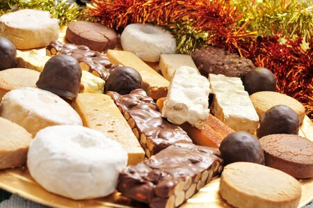 confections: closeup of a golden tray with different turron, mantecados and polvorones, typical christmas confections in Spain Stock Photo