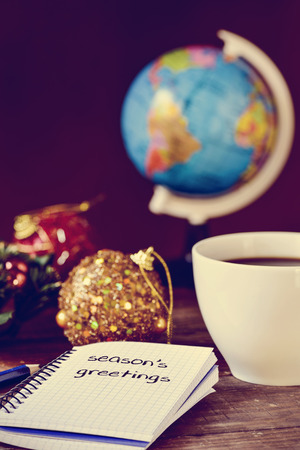 migrated: closeup of a notebook with the text seasons greetings written in it on a rustic wooden table with some christmas ornaments, a cup of coffee and a globe Stock Photo