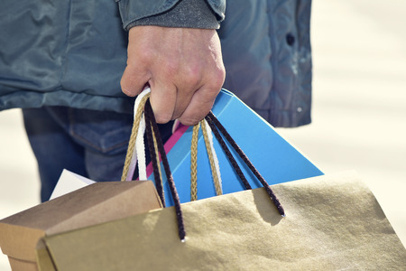 consumerism: closeup of a young caucasian man carrying some different paper shopping bags in the street