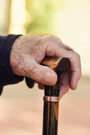 gerontology: closeup of the hand of an old caucasian man with a walking stick, outdoors