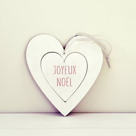 a white heart-shaped ornament with the text joyeux noel, merry christmas in french, written in red, on a white surface against a white background