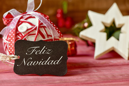 feliz navidad: a black label with the text feliz navidad, merry christmas in spanish, and some different cozy christmas ornaments on a red rustic wooden surface