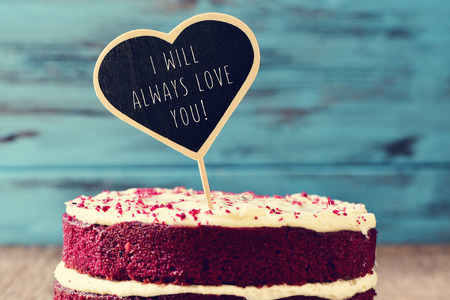 closeup of a red velvet cake topped with a heart-shaped chalkboard with the text I will always love you written in it, on a rustic wooden table Stock Photo